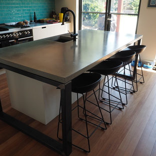 Contemporary eat-in kitchen appliance - Eat-in kitchen - contemporary galley medium tone wood floor and green floor eat-in kitchen idea in Melbourne with a single-bowl sink, concrete countertops, green backsplash, glass tile backsplash, stainless steel appliances and an island