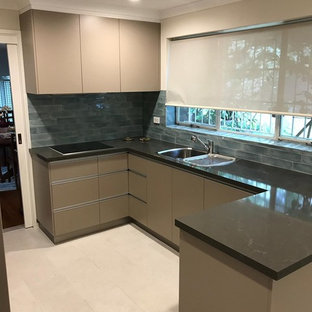 Inspiration for a mid-sized modern u-shaped separate kitchen in Canberra - Queanbeyan with a double-bowl sink, flat-panel cabinets, beige cabinets, quartz benchtops, blue splashback, ceramic splashback, panelled appliances, ceramic floors, yellow floor and orange benchtop.