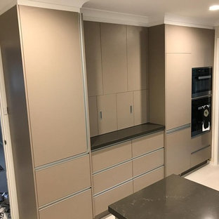 Mid-sized modern u-shaped separate kitchen in Canberra - Queanbeyan with a double-bowl sink, flat-panel cabinets, beige cabinets, quartz benchtops, blue splashback, ceramic splashback, panelled appliances, ceramic floors, yellow floor and orange benchtop.