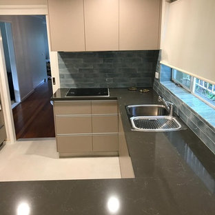 Photo of a mid-sized modern u-shaped separate kitchen in Canberra - Queanbeyan with a double-bowl sink, flat-panel cabinets, beige cabinets, quartz benchtops, blue splashback, ceramic splashback, panelled appliances, ceramic floors, yellow floor and orange benchtop.