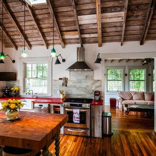 Неиссякаемый источник вдохновения для домашнего уюта: кухня в стиле кантри с обеденным столом, столешницей из кварцевого композита, островом, раковиной в стиле кантри, техникой из нержавеющей стали, темным паркетным полом и красной столешницей
