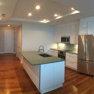 Design ideas for a modern open plan kitchen in Atlanta with an undermount sink, flat-panel cabinets, white cabinets, quartz benchtops, green splashback, mosaic tile splashback, stainless steel appliances, laminate floors and green benchtop.