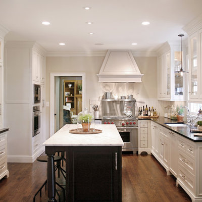 Example of a large classic u-shaped medium tone wood floor and brown floor kitchen design in Atlanta with an undermount sink, recessed-panel cabinets, white cabinets, paneled appliances, white backsplash, solid surface countertops and an island