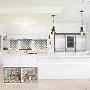 メルボルンの大きいコンテンポラリースタイルのおしゃれなキッチン (フラットパネル扉のキャビネット、白いキャビネット、クオーツストーンカウンター、マルチカラーのキッチンパネル、ガラス板のキッチンパネル、シルバーの調理設備の、セラミックタイルの床) の写真