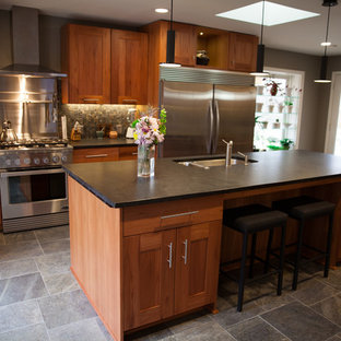 This is an example of a mid-sized midcentury single-wall open plan kitchen in Indianapolis with a double-bowl sink, shaker cabinets, dark wood cabinets, soapstone benchtops, grey splashback, stone tile splashback, stainless steel appliances, slate floors, with island and grey floor.