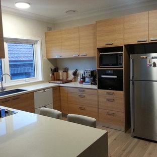 シドニーの中サイズのアジアンスタイルのおしゃれなキッチン (シングルシンク、フラットパネル扉のキャビネット、淡色木目調キャビネット、クオーツストーンカウンター、ベージュキッチンパネル、石スラブのキッチンパネル、淡色無垢フローリング、黒い調理設備) の写真