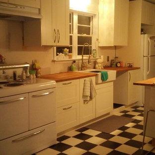 ダラスの中サイズのエクレクティックスタイルのおしゃれなキッチン (エプロンフロントシンク、シェーカースタイル扉のキャビネット、白いキャビネット、木材カウンター、白い調理設備) の写真