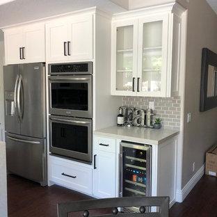 オレンジカウンティの中サイズのカントリー風おしゃれなキッチン (エプロンフロントシンク、シェーカースタイル扉のキャビネット、白いキャビネット、珪岩カウンター、グレーのキッチンパネル、サブウェイタイルのキッチンパネル、シルバーの調理設備の、濃色無垢フローリング、マルチカラーの床、ベージュのキッチンカウンター) の写真