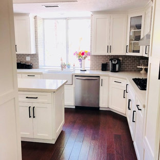 Mid-sized country u-shaped eat-in kitchen in Orange County with a farmhouse sink, shaker cabinets, white cabinets, quartzite benchtops, grey splashback, subway tile splashback, stainless steel appliances, dark hardwood floors, with island, multi-coloured floor and beige benchtop.