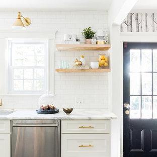 Modelo de cocina comedor de galera, moderna, pequeña, con fregadero bajoencimera, puertas de armario blancas, encimera de mármol, salpicadero blanco, salpicadero de azulejos tipo metro, electrodomésticos de acero inoxidable, suelo de pizarra y una isla
