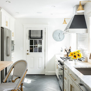 Small transitional eat-in kitchen ideas - Small transitional galley slate floor eat-in kitchen photo in Boston with an undermount sink, white cabinets, marble countertops, white backsplash, subway tile backsplash, stainless steel appliances and an island