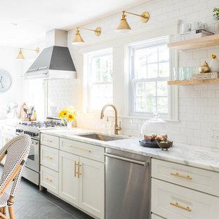 Foto de cocina comedor moderna, pequeña, con fregadero bajoencimera, puertas de armario blancas, encimera de mármol, salpicadero blanco, salpicadero de azulejos tipo metro, electrodomésticos de acero inoxidable, suelo de pizarra y una isla
