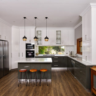 Photo of a large transitional u-shaped eat-in kitchen in Other with a drop-in sink, raised-panel cabinets, white cabinets, quartz benchtops, white splashback, subway tile splashback, with island, brown floor, white benchtop, stainless steel appliances and dark hardwood floors.