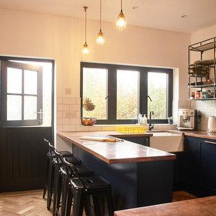Geschlossene, Kleine Industrial Küche in U-Form mit Landhausspüle, Schrankfronten im Shaker-Stil, blauen Schränken, Kupfer-Arbeitsplatte, Küchenrückwand in Weiß, Rückwand aus Metrofliesen und Küchengeräten aus Edelstahl in Sussex
