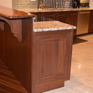 Große Klassische Wohnküche ohne Insel in U-Form mit Doppelwaschbecken, profilierten Schrankfronten, dunklen Holzschränken, Granit-Arbeitsplatte, Küchenrückwand in Grau, Glasrückwand, Küchengeräten aus Edelstahl und Keramikboden in Sonstige