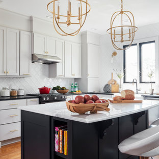 Design ideas for a mid-sized transitional l-shaped eat-in kitchen in Other with a farmhouse sink, shaker cabinets, grey cabinets, soapstone benchtops, white splashback, mosaic tile splashback, black appliances, medium hardwood floors, with island, brown floor and black benchtop.
