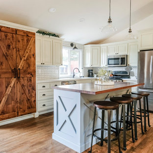 Large farmhouse kitchen photos - Example of a large country l-shaped medium tone wood floor kitchen design in Other with an island, an undermount sink, raised-panel cabinets, white cabinets, white backsplash, stainless steel appliances and white countertops