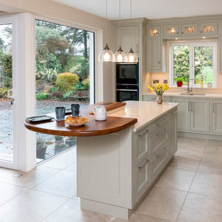 Inspiration for a mid-sized country l-shaped eat-in kitchen in Cork with a double-bowl sink, flat-panel cabinets, green cabinets, quartzite benchtops, beige splashback, stainless steel appliances, porcelain floors, with island, beige floor and beige benchtop.