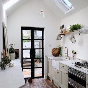 サセックスの小さいコンテンポラリースタイルのおしゃれなキッチン (エプロンフロントシンク、シェーカースタイル扉のキャビネット、緑のキャビネット、大理石カウンター、シルバーの調理設備、無垢フローリング、アイランドなし、茶色い床、白いキッチンカウンター) の写真