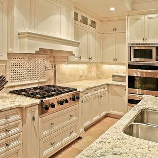 Mittelgroße Klassische Küche in L-Form mit Doppelwaschbecken, flächenbündigen Schrankfronten, weißen Schränken, Granit-Arbeitsplatte, Küchenrückwand in Beige, Kalk-Rückwand, Küchengeräten aus Edelstahl, Porzellan-Bodenfliesen, Kücheninsel und rosa Boden in New York
