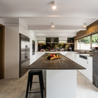 Photo of an industrial u-shaped kitchen in Melbourne with a single-bowl sink, flat-panel cabinets, white cabinets, black splashback, stone slab splashback, stainless steel appliances, with island, grey floor and black benchtop.