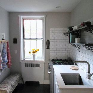 Geschlossene, Zweizeilige, Kleine Landhaus Küche ohne Insel mit Einbauwaschbecken, flächenbündigen Schrankfronten, weißen Schränken, Quarzwerkstein-Arbeitsplatte, Küchenrückwand in Weiß, Rückwand aus Metrofliesen, weißen Elektrogeräten und Vinylboden in New York