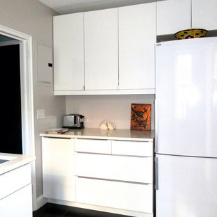 Photo of a small modern galley separate kitchen in New York with a drop-in sink, flat-panel cabinets, white cabinets, quartz benchtops, white splashback, subway tile splashback, white appliances, vinyl floors, no island and black floor.