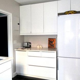 ニューヨークの小さいモダンスタイルのおしゃれなキッチン (ドロップインシンク、フラットパネル扉のキャビネット、白いキャビネット、クオーツストーンカウンター、白いキッチンパネル、サブウェイタイルのキッチンパネル、白い調理設備、クッションフロア、アイランドなし、黒い床) の写真