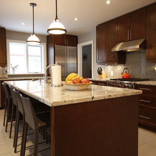 Mittelgroße Klassische Wohnküche in L-Form mit Unterbauwaschbecken, Schrankfronten mit vertiefter Füllung, braunen Schränken, Granit-Arbeitsplatte, Küchenrückwand in Beige, Rückwand aus Stäbchenfliesen, Küchengeräten aus Edelstahl, Porzellan-Bodenfliesen, Kücheninsel und beigem Boden in Toronto