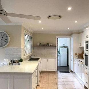 シドニーの中くらいのカントリー風おしゃれなキッチン (ダブルシンク、シェーカースタイル扉のキャビネット、白いキャビネット、珪岩カウンター、グレーのキッチンパネル、白い調理設備、アイランドなし、ピンクの床) の写真