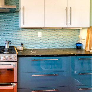 Inredning av ett modernt mellanstort svart svart kök, med släta luckor, vita skåp, blått stänkskydd, rostfria vitvaror, linoleumgolv, en halv köksö, orange golv, en nedsänkt diskho, granitbänkskiva och stänkskydd i mosaik
