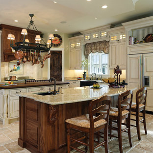 Photo of a large country single-wall separate kitchen in DC Metro with raised-panel cabinets, white cabinets, beige splashback, a farmhouse sink, granite benchtops, stone tile splashback, panelled appliances, travertine floors, multiple islands and beige floor.