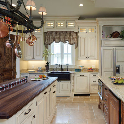 Enclosed kitchen - large country single-wall travertine floor and beige floor enclosed kitchen idea in DC Metro with a farmhouse sink, raised-panel cabinets, white cabinets, granite countertops, beige backsplash, stone tile backsplash, paneled appliances and two islands