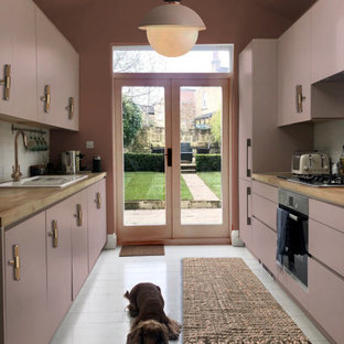Design ideas for a mid-sized contemporary galley separate kitchen in London with a drop-in sink, flat-panel cabinets, pink cabinets, wood benchtops, white splashback, ceramic splashback, stainless steel appliances, painted wood floors, no island, white floor and beige benchtop.