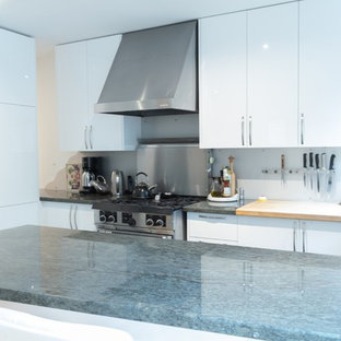 Photo of a mid-sized modern l-shaped open plan kitchen in Toronto with an undermount sink, flat-panel cabinets, white cabinets, granite benchtops, grey splashback, metal splashback, stainless steel appliances, ceramic floors, a peninsula, green floor and green benchtop.