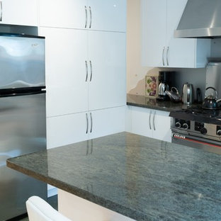 Design ideas for a mid-sized modern l-shaped open plan kitchen in Toronto with an undermount sink, flat-panel cabinets, white cabinets, granite benchtops, grey splashback, metal splashback, stainless steel appliances, ceramic floors, a peninsula, green floor and green benchtop.