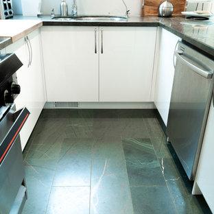 トロントの中サイズのモダンスタイルのおしゃれなキッチン (アンダーカウンターシンク、フラットパネル扉のキャビネット、白いキャビネット、御影石カウンター、グレーのキッチンパネル、メタルタイルのキッチンパネル、シルバーの調理設備の、セラミックタイルの床、緑の床、緑のキッチンカウンター) の写真