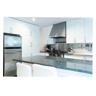 Новый формат декора квартиры: угловая кухня-гостиная среднего размера в стиле модернизм с врезной раковиной, плоскими фасадами, белыми фасадами, столешницей из гранита, серым фартуком, фартуком из металлической плитки, техникой из нержавеющей стали, полом из керамической плитки, полуостровом, зеленым полом и зеленой столешницей