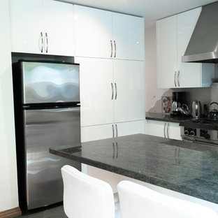 This is an example of a mid-sized modern l-shaped open plan kitchen in Toronto with an undermount sink, flat-panel cabinets, white cabinets, granite benchtops, grey splashback, metal splashback, stainless steel appliances, ceramic floors, a peninsula, green floor and green benchtop.