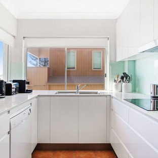 Small modern u-shaped kitchen in Gold Coast - Tweed with an undermount sink, flat-panel cabinets, white cabinets, glass sheet splashback, orange floor and grey benchtop.