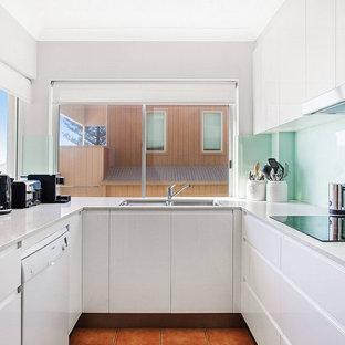 Modelo de cocina en U, minimalista, pequeña, con fregadero bajoencimera, armarios con paneles lisos, puertas de armario blancas, salpicadero de vidrio templado, suelo naranja y encimeras grises