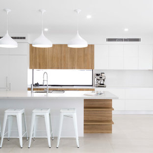 Design ideas for a contemporary galley kitchen in Gold Coast - Tweed with an undermount sink, flat-panel cabinets, white cabinets, white splashback, panelled appliances, with island, beige floor and white benchtop.