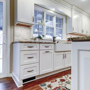 Стильный дизайн: п-образная кухня в стиле современная классика с обеденным столом, раковиной в стиле кантри, белыми фасадами, гранитной столешницей, белым фартуком, фартуком из травертина, техникой из нержавеющей стали, пробковым полом, островом и коричневым полом - последний тренд