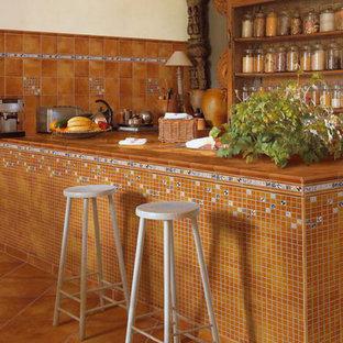 サンフランシスコの小さい地中海スタイルのおしゃれなキッチン (オープンシェルフ、濃色木目調キャビネット、タイルカウンター、茶色いキッチンパネル、セラミックタイルのキッチンパネル、シルバーの調理設備の、テラコッタタイルの床) の写真