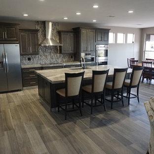 ラスベガスの大きいモダンスタイルのおしゃれなキッチン (アンダーカウンターシンク、レイズドパネル扉のキャビネット、グレーのキャビネット、御影石カウンター、グレーのキッチンパネル、モザイクタイルのキッチンパネル、シルバーの調理設備の、セラミックタイルの床、グレーの床、グレーのキッチンカウンター) の写真