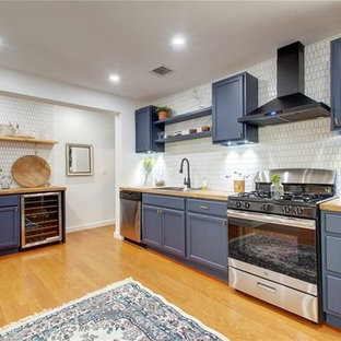 Design ideas for a mid-sized country l-shaped eat-in kitchen in Austin with a single-bowl sink, louvered cabinets, blue cabinets, wood benchtops, white splashback, ceramic splashback, stainless steel appliances, laminate floors, no island, brown floor and brown benchtop.