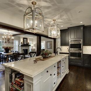 Große Klassische Wohnküche in U-Form mit profilierten Schrankfronten, grauen Schränken, Küchenrückwand in Weiß, Küchengeräten aus Edelstahl, dunklem Holzboden, Kücheninsel, braunem Boden, Landhausspüle, Mineralwerkstoff-Arbeitsplatte und Rückwand aus Glasfliesen in Minneapolis