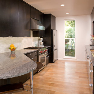 ミネアポリスの広いコンテンポラリースタイルのおしゃれなキッチン (アンダーカウンターシンク、フラットパネル扉のキャビネット、濃色木目調キャビネット、白いキッチンパネル、ボーダータイルのキッチンパネル、シルバーの調理設備、淡色無垢フローリング、茶色い床、御影石カウンター) の写真
