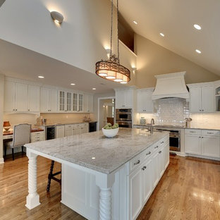 Photo of a large classic l-shaped kitchen/diner in Minneapolis with a submerged sink, white cabinets, white splashback, an island, white appliances, ceramic splashback, granite worktops, brown floors, recessed-panel cabinets and medium hardwood flooring.