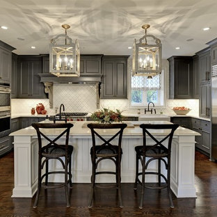 Large transitional eat-in kitchen inspiration - Large transitional u-shaped dark wood floor and brown floor eat-in kitchen photo in Minneapolis with gray cabinets, white backsplash, stainless steel appliances, an island, raised-panel cabinets, a farmhouse sink, solid surface countertops, white countertops and ceramic backsplash